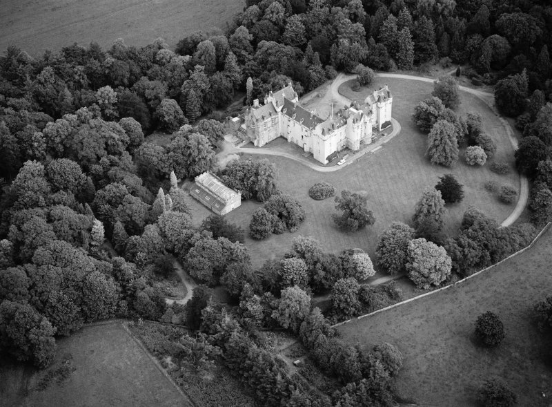 Oblique aerial view centred on Fyvie Castle with the racquets court adjacent, looking to the NE.
