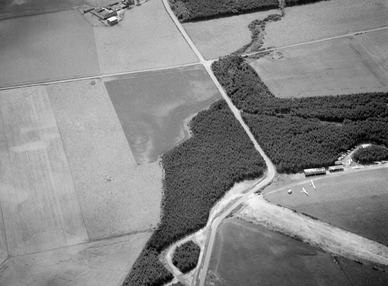 Oblique aerial view centred on the cropmarks of the unenclosed settlement, ring ditches and enclosures at Lower Auchenreath with Dallachy airfield adjacent, looking to the SE.