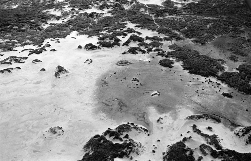 Oblique aerial view centred on the remains of hut circles and the midden at Sands of Forvie, looking to the NE.
