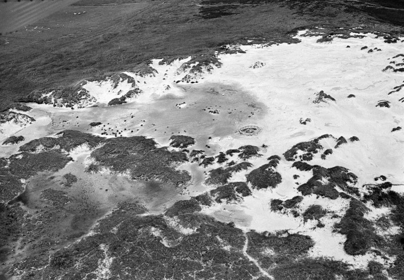 Oblique aerial view centred on the remains of hut circles and the midden at Sands of Forvie, looking to the SW.