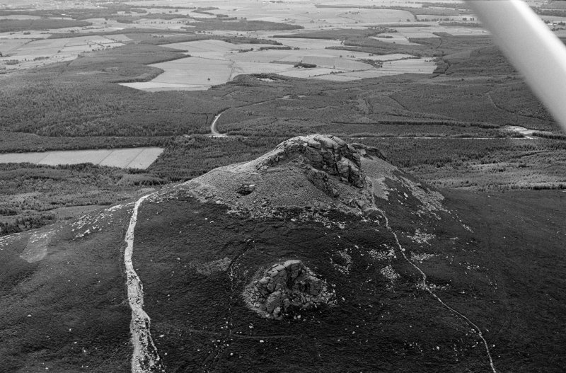 Oblique aerial view centred on the remains of the fort at Mither Tap of Bennachie, looking to the SSE.
