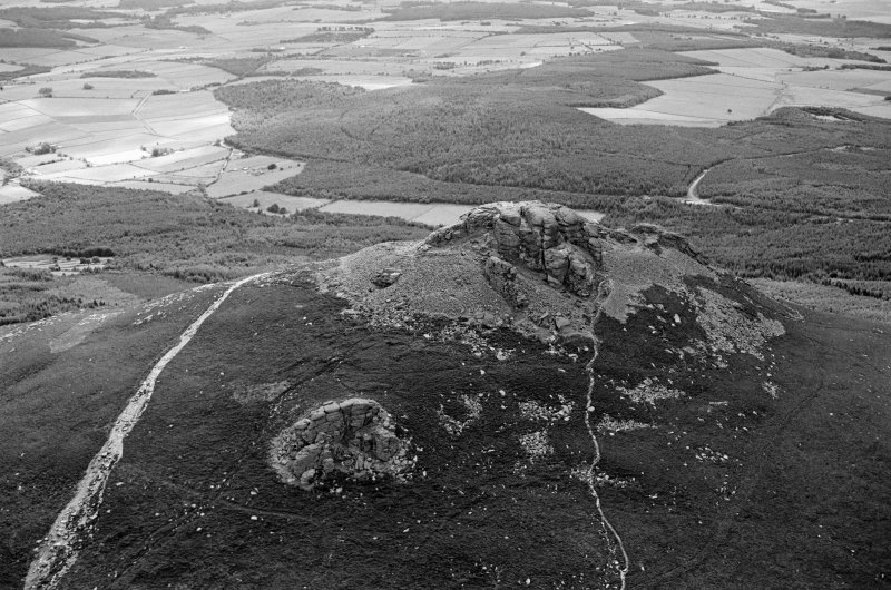 Oblique aerial view centred on the remains of the fort at Mither Tap of Bennachie, looking to the SE.