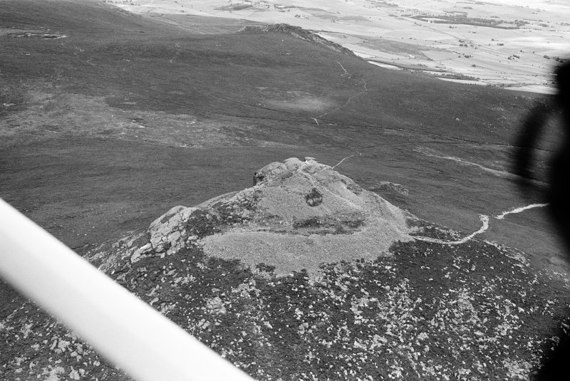 Oblique aerial view centred on the remains of the fort at Mither Tap of Bennachie, looking to the WNW.