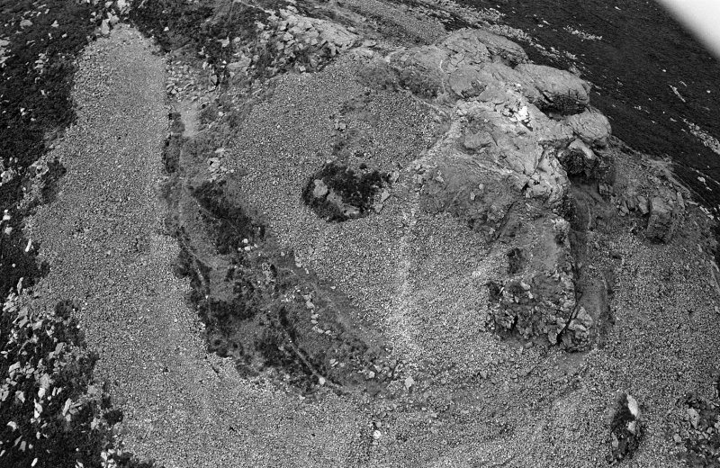 Oblique aerial view centred on the remains of the fort at Mither Tap of Bennachie, looking to the WSW.
