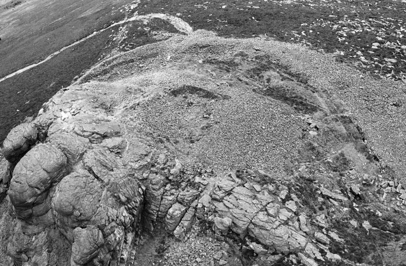 Oblique aerial view centred on the remains of the fort at Mither Tap of Bennachie, looking to the NE.