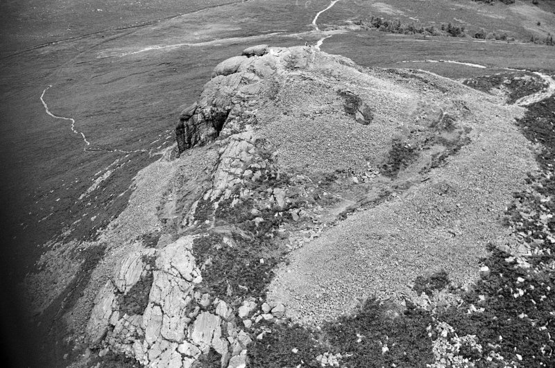Oblique aerial view centred on the remains of the fort at Mither Tap of Bennachie, looking to the NNW.