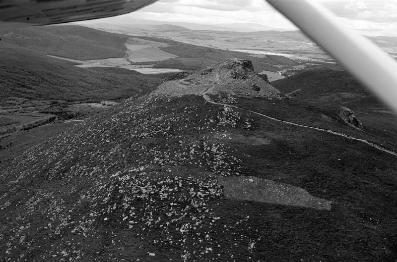 Oblique aerial view centred on the remains of the fort at Mither Tap of Bennachie, looking to the SSW.