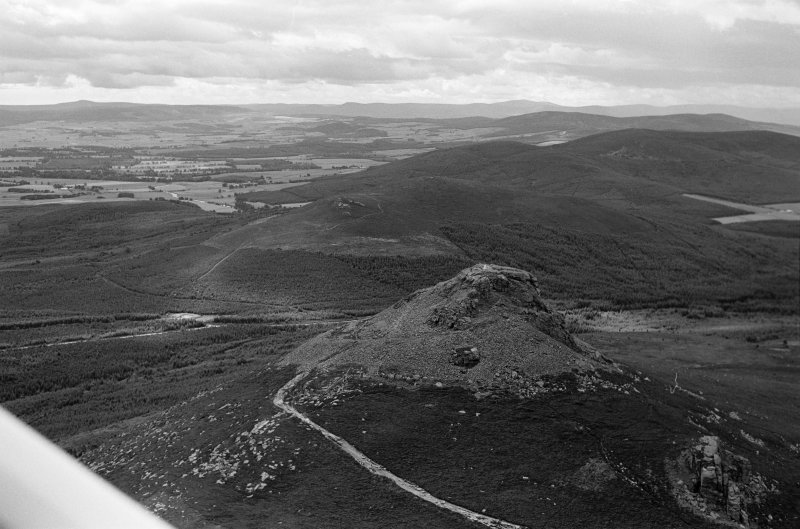 Oblique aerial view centred on the remains of the fort at Mither Tap of Bennachie, looking to the S.