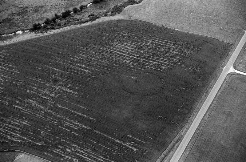 Oblique aerial view centred on the cropmarks of the circular enclosure at Barflat, looking to the SSE.