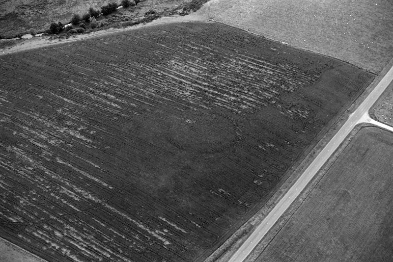 Oblique aerial view centred on the cropmarks of the circular enclosure at Barflat, looking to the SE.