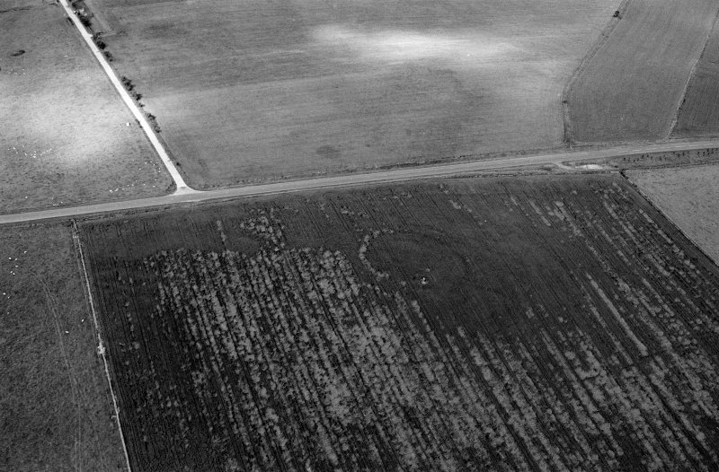 Oblique aerial view centred on the cropmarks of the circular enclosure at Barflat, looking to the WNW.