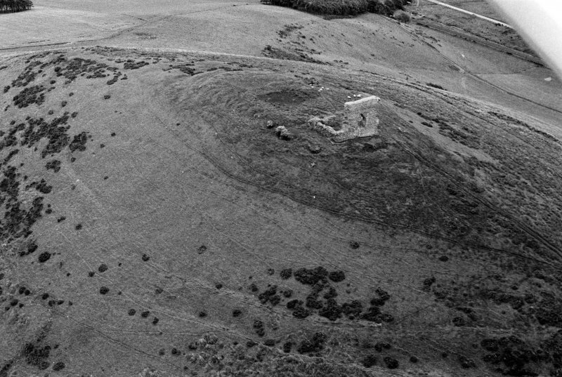 Oblique aerial view centred on the remains of the tower house and fort at Dunideer, looking to the SSE.