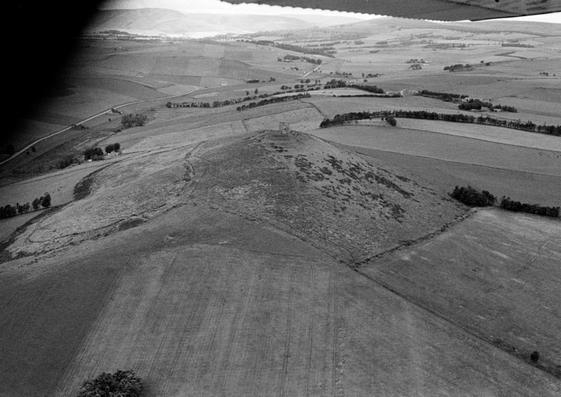 Oblique aerial view centred on the remains of the tower house and fort at Dunideer, looking to the E.