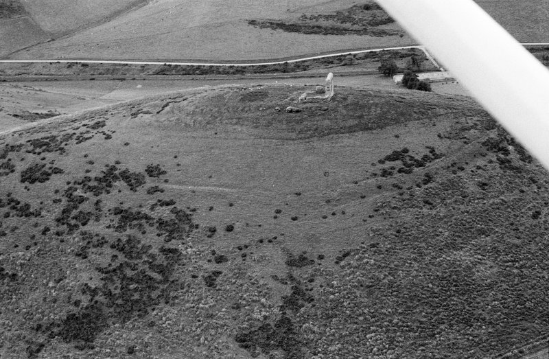 Oblique aerial view centred on the remains of the tower house and fort at Dunideer, looking to the SSW.