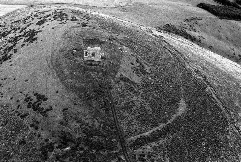 Oblique aerial view centred on the remains of the tower house and fort at Dunideer, looking to the ESE.
