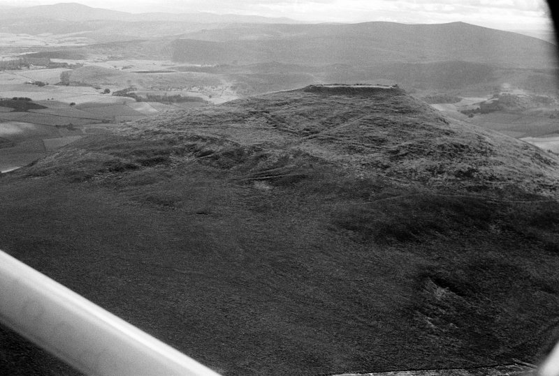 Oblique aerial view centred on the remains of the vitrified fort at Tap O' Noth, looking to the SW.