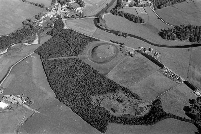 Oblique aerial view centred on the remains of the castle and motte of Doune of Invernochty, looking to the E.