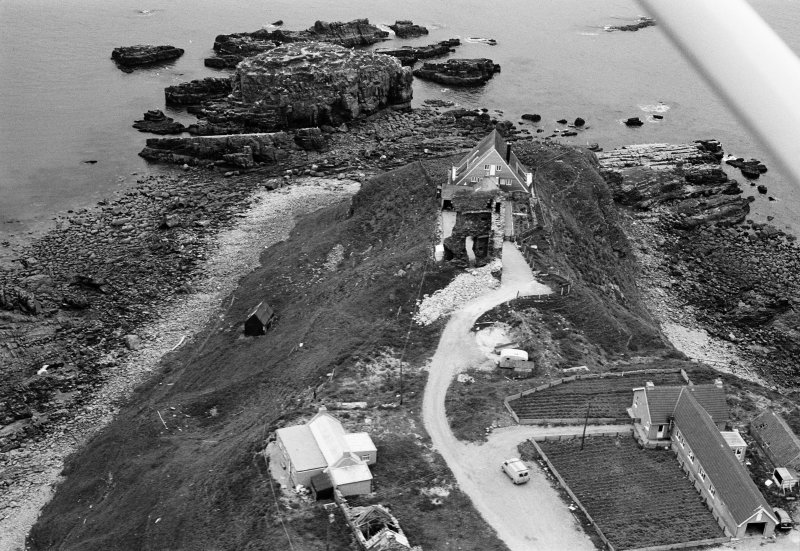 Oblique aerial view centred on the remains of Old Slains Castle with the house and village adjacent, looking to the ESE.