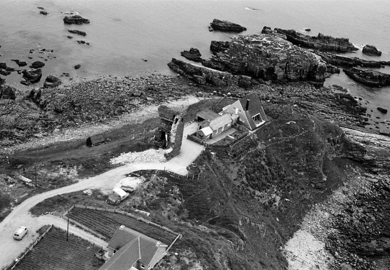 Oblique aerial view centred on the remains of Old Slains Castle with the house and village adjacent, looking to the E.
