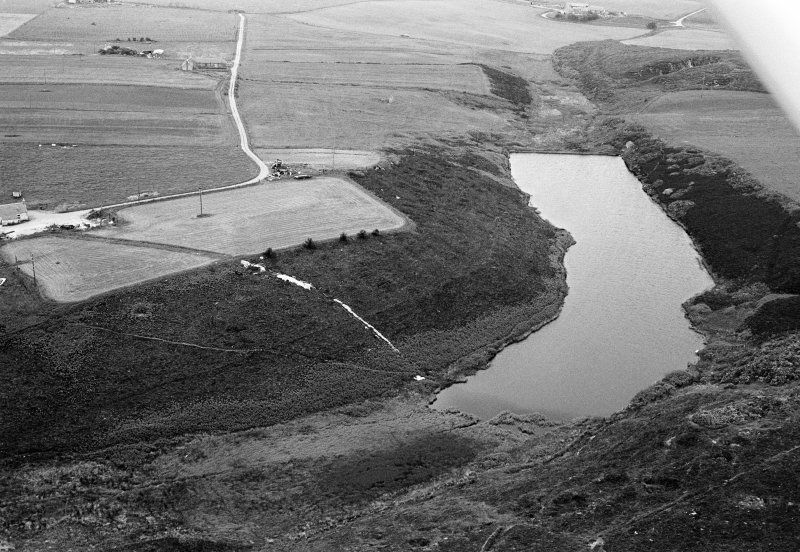Oblique aerial view centred on the Den of Boddam reservoir, flint mines and lithic working site, looking to the NNE.