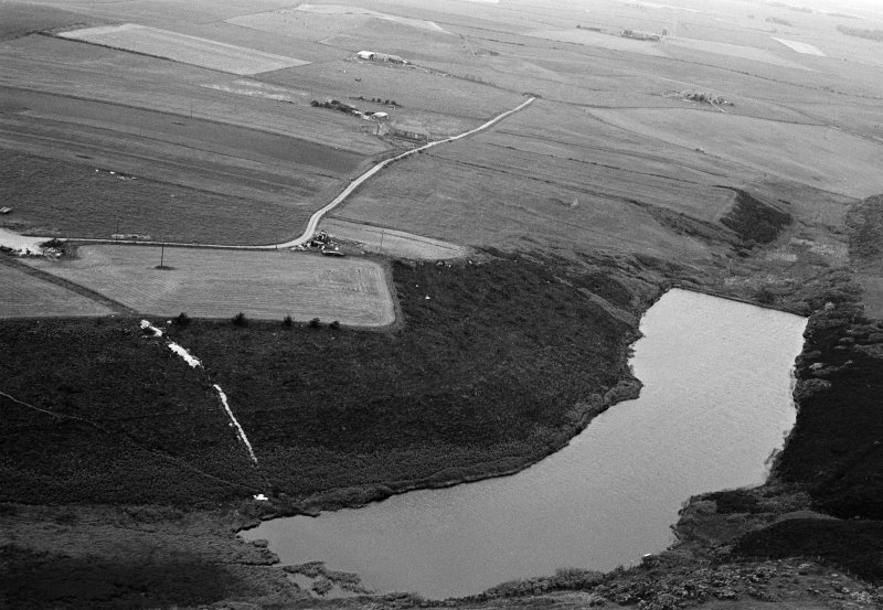 Oblique aerial view centred on the Den of Boddam reservoir, flint mines and lithic working site, looking to the NW.