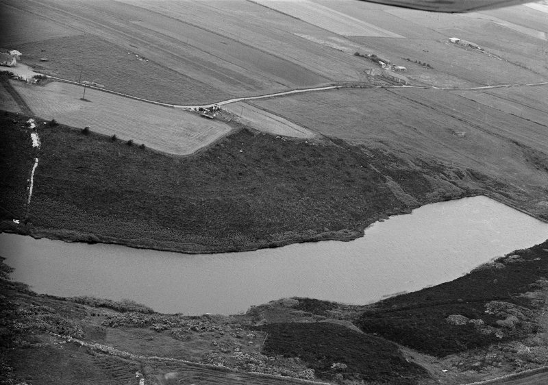 Oblique aerial view centred on the Den of Boddam reservoir, flint mines and lithic working site, looking to the WNW.