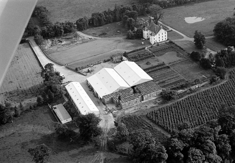 Oblique aerial view centred on Gallery House and gardens with cropmarks adjacent, looking to the SSW.