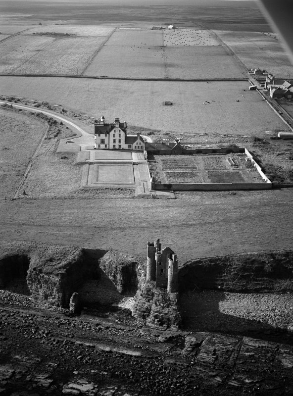 Oblique aerial view centred on the remains of Old Keiss Castle with Keiss Castle and walled garden adjacent, looking to the NW.