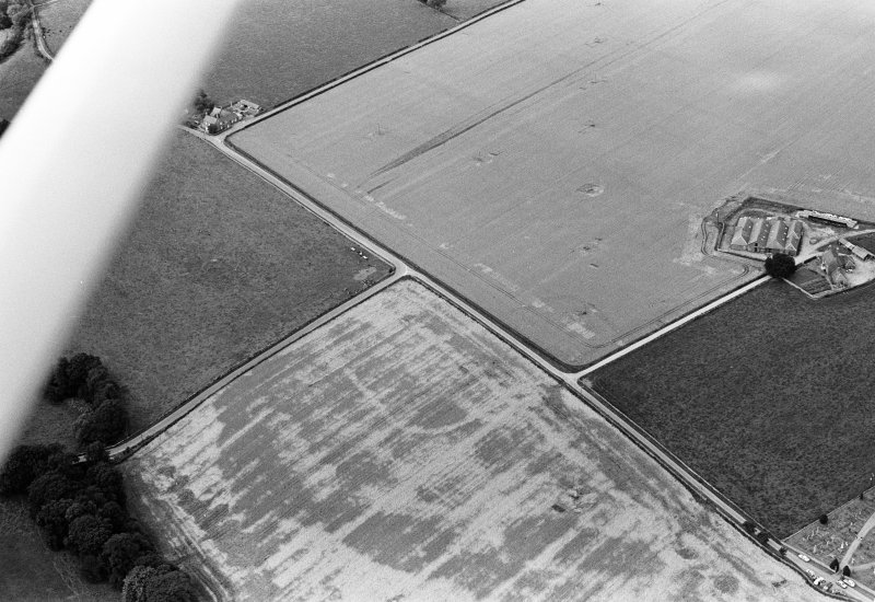 Oblique aerial view centred on the cropmarks of the Roman Temporary Camp at Stracathro, looking to the WNW.
