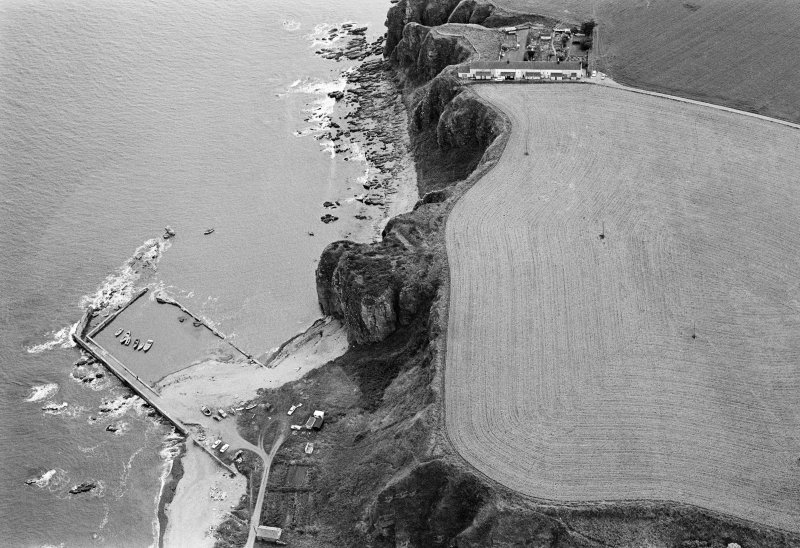 Oblique aerial view centred on the remains of the promontory fort at Castle Rock, Auchmithie with the harbour and coastguard station cottages adjacent, looking to the SE.