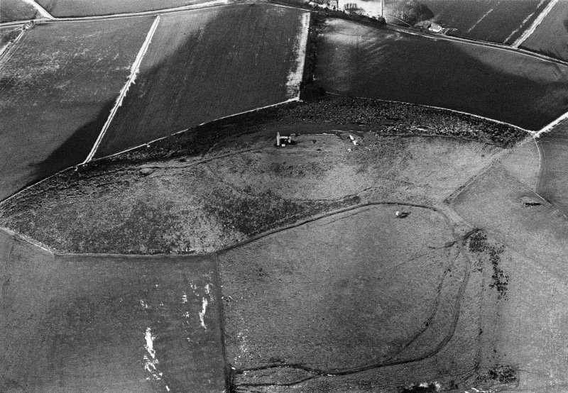 Oblique aerial view centred on the remains of the tower house and fort at Dunideer, looking to the NE.