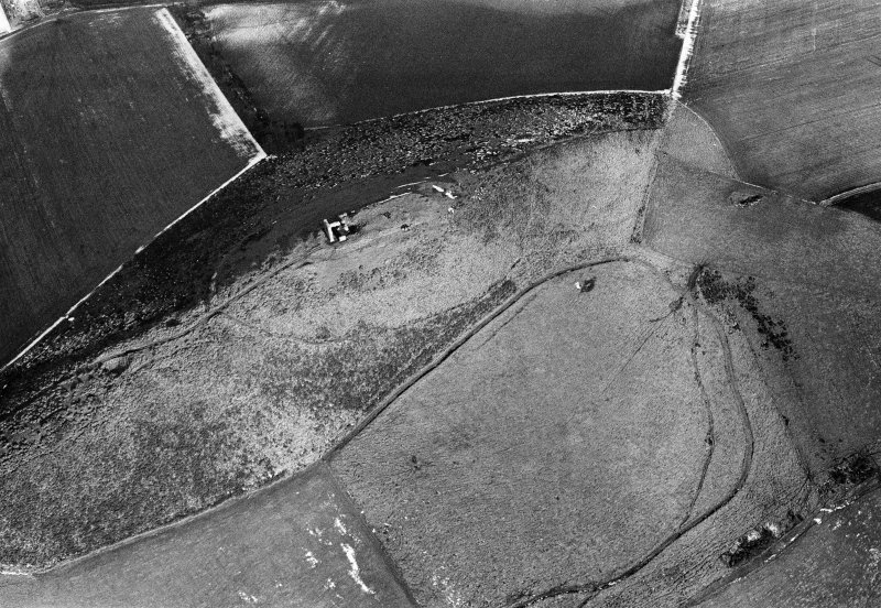 Oblique aerial view centred on the remains of the tower house and fort at Dunideer, looking to the ENE.