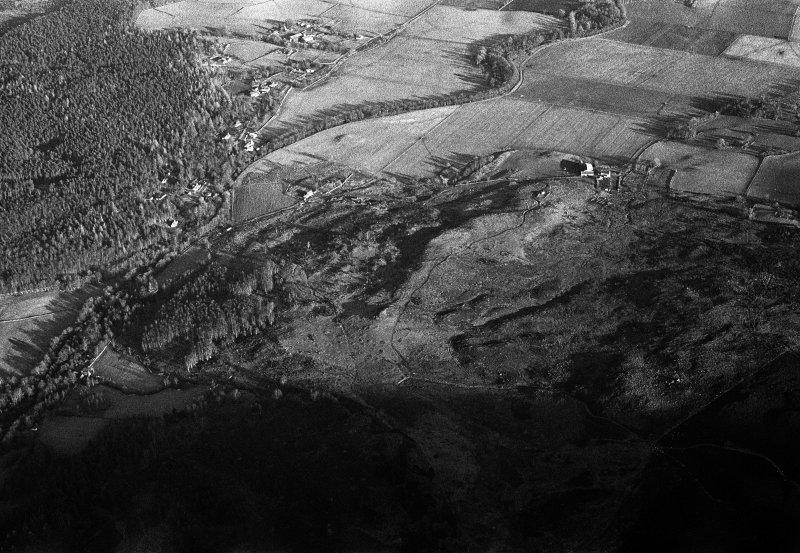 Oblique aerial view centred on the remains of hut circles, clearance cairns, buildings and enclosures at Wester Clune, looking to the NE.
