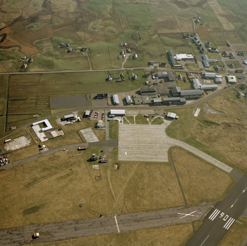 Oblique aerial view centred on Balivanich village with Benbecula airfield adjacent, taken from the NNE.