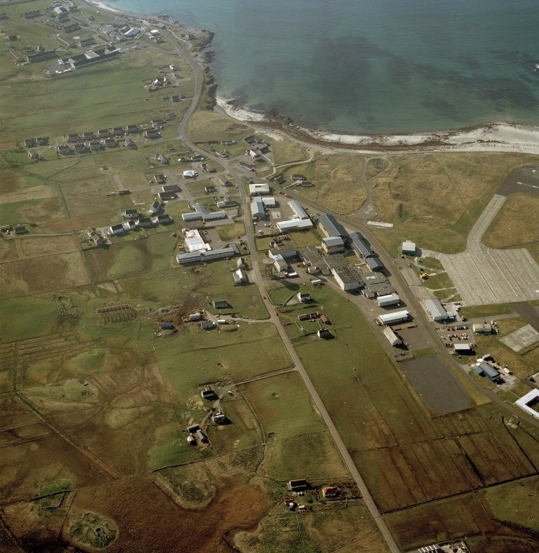 Oblique aerial view centred on Balivanich village with Benbecula airfield adjacent, taken from the SE.