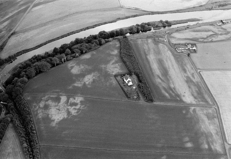 Oblique aerial view centred on the cropmarks of the palisaded enclosure, square and round barrows at Fisherhills, looking to the NNE.