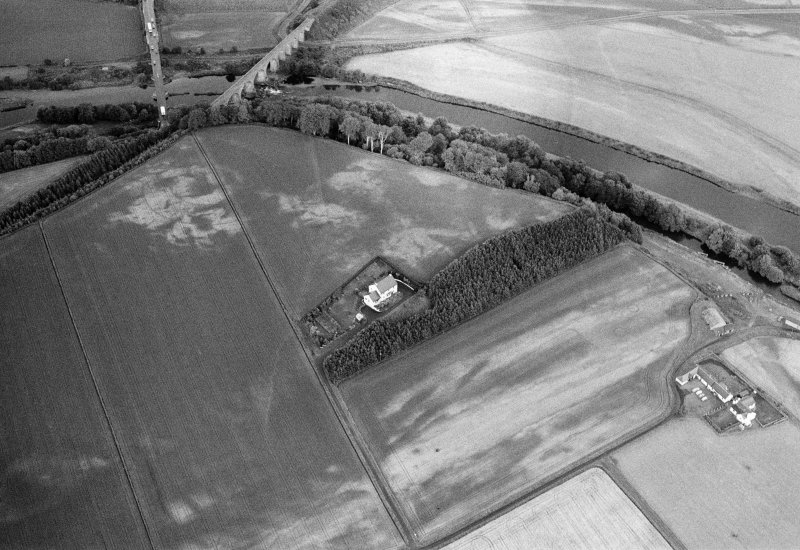 Oblique aerial view centred on the cropmarks of the palisaded enclosure, square and round barrows at Fisherhills with the North Water viaduct adjacent, looking to the WNW.