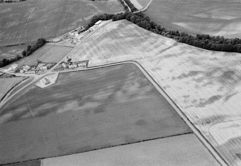 Oblique aerial view centred on the cropmarks of the pit defined cursus, unenclosed settlement, ring ditches, pits and rig with Stracathro Roman Temporary Camp adjacent at Inchbare North, looking to the NW.