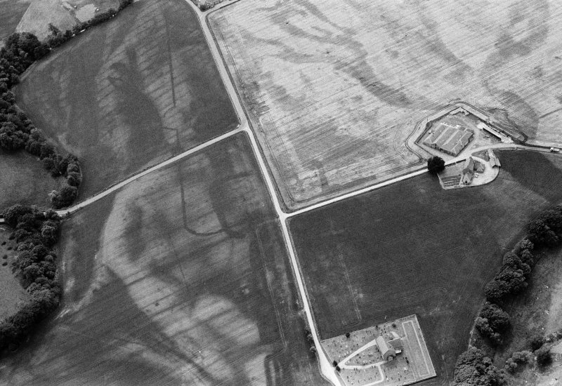 Oblique aerial view centred on the cropmarks of the Roman Temporary Camp and Fort with the churchyard adjacent at Stracathro, looking to the SW.
