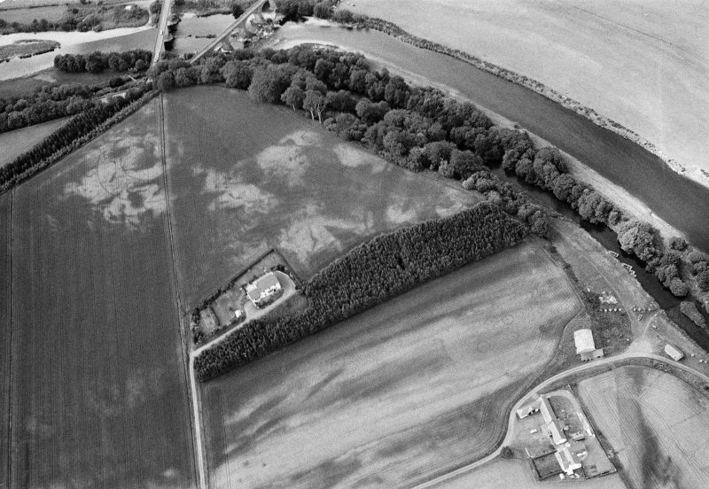 Oblique aerial view centred on the cropmarks of the palisaded enclosure, square and round barrows at Fisherhills, looking to the W.