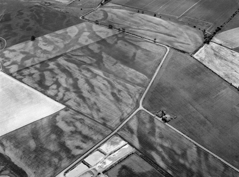 Oblique aerial view centred on the cropmarks of the pit defined cursus, enclosed cremation cemetery, ring ditch and rig at Balneaves, looking to the SE.