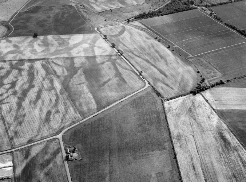 Oblique aerial view centred on the cropmarks of the pit defined cursus, enclosed cremation cemetery, rectilinear enclosure, ring ditch and rig at Balneaves, looking to the ESE.