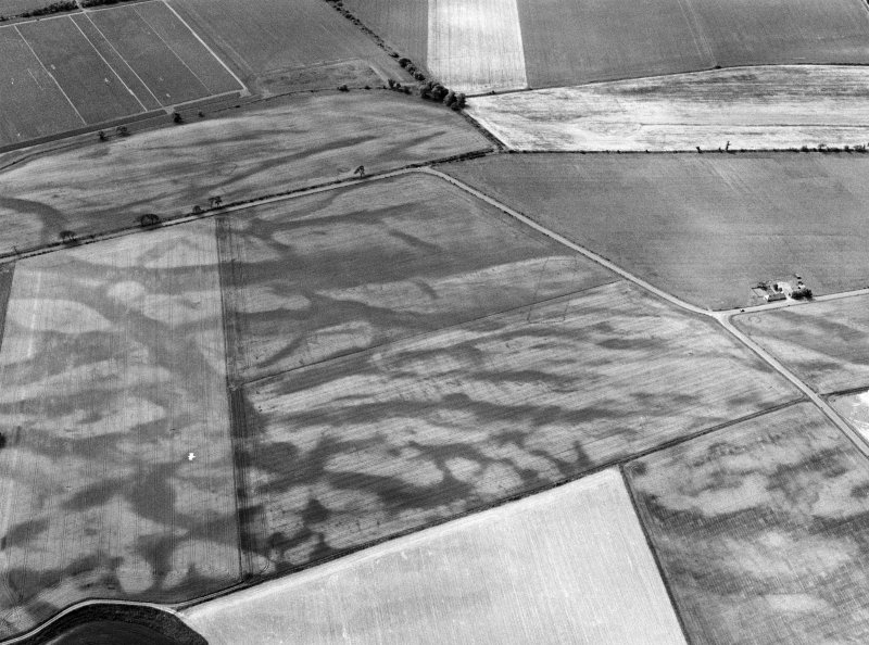 Oblique aerial view centred on the cropmarks of the pit defined cursus, enclosed cremation cemetery, rectilinear enclosure, ring ditch and rig at Balneaves, looking to the SSE.