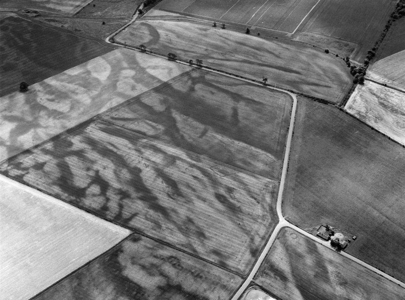 Oblique aerial view centred on the cropmarks of the pit defined cursus, enclosed cremation cemetery, rectilinear enclosure, ring ditch and rig at Balneaves, looking to the SE.