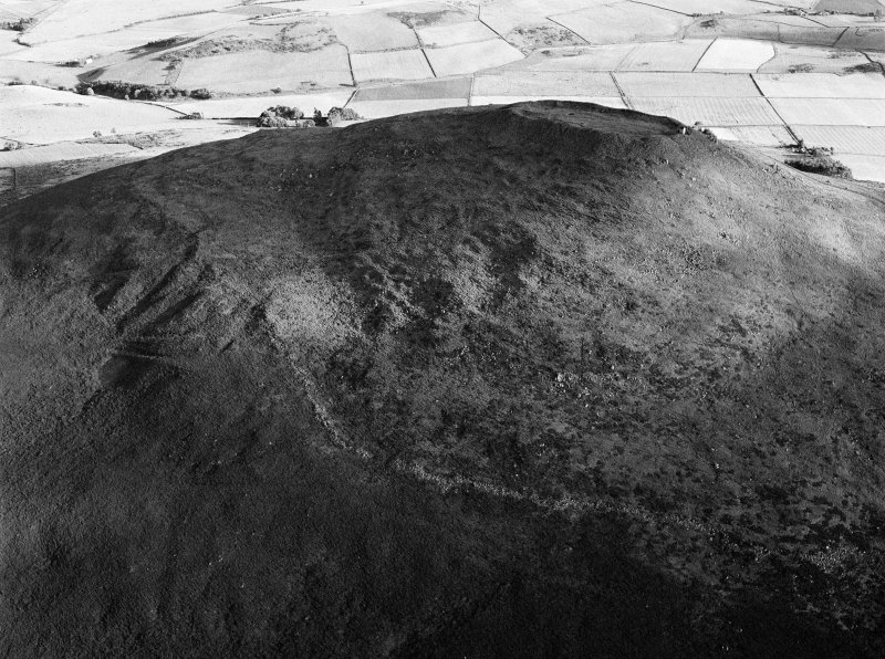 Oblique aerial view centred on the remains of the vitrified fort at Tap O' Noth, looking to the SSW.