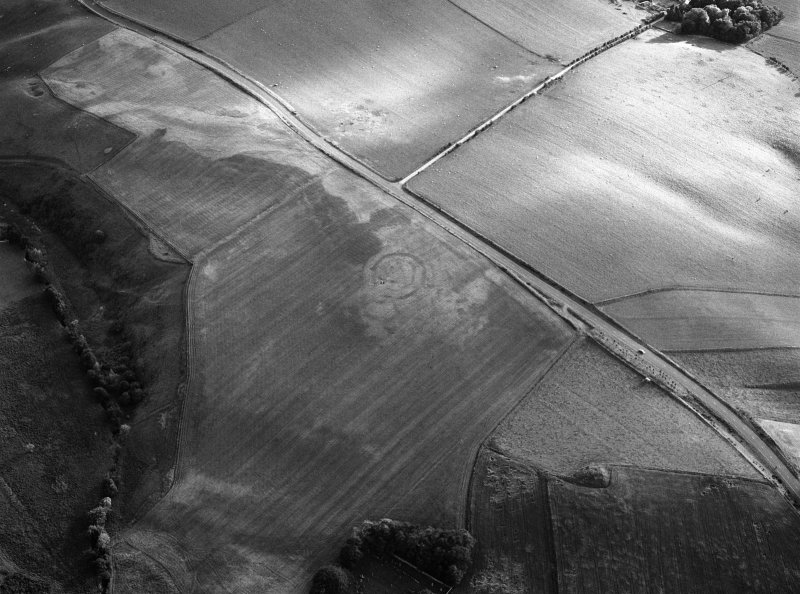 Oblique aerial view centred on the cropmarks of the circular enclosure at Barflat, looking to the SW.
