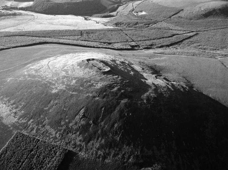 Oblique aerial view centred on the remains of the vitrified fort at Tap O' Noth, looking to the N.