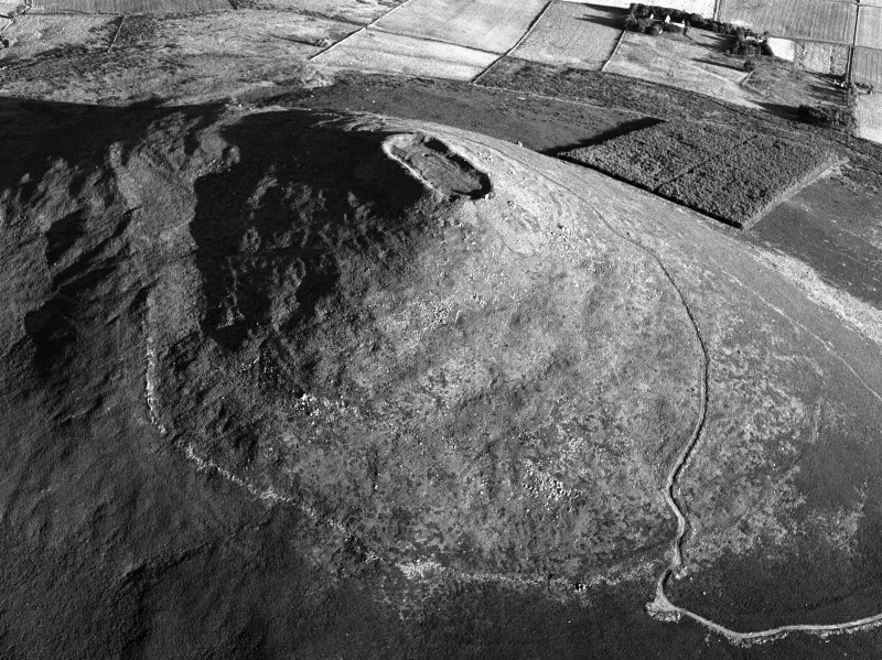 Oblique aerial view centred on the remains of the vitrified fort at Tap O' Noth, looking to the SE.