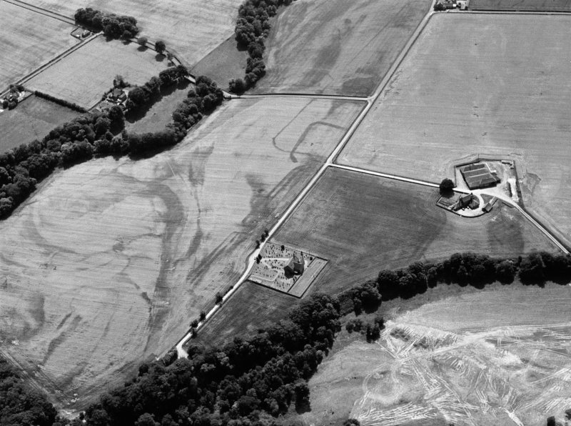 Oblique aerial view centred on the cropmarks of the Roman Temporary Camp, ring ditch and pits with Strathcathro Parish Church adjacent, looking to the SSW.