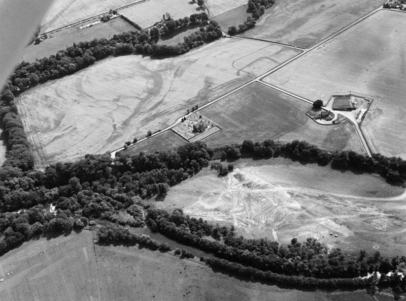 Oblique aerial view centred on the cropmarks of the Roman Temporary Camp, ring ditch and pits with Strathcathro Parish Church adjacent, looking to the S.